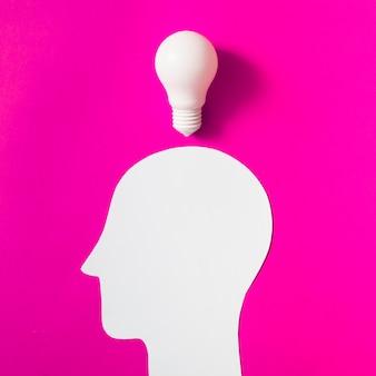 Glühlampe über dem herausgeschnittenen weißen menschlichen Kopf auf rosa Hintergrund