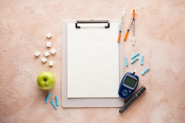 Glukometer, lanzettenstift, apfel und spritzen