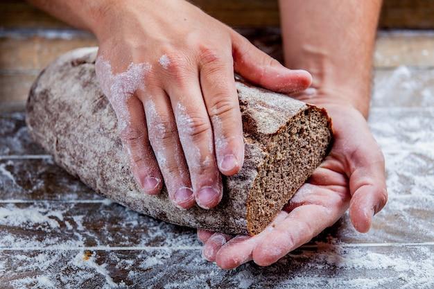 Glutenfrei gebackenes brot in bäckerhänden auf holz
