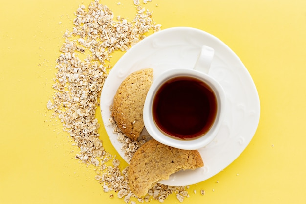 Glutenfreie hausgemachte hafer haferkekse und eine tasse tee oder kaffee espresso auf pastellgelb