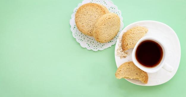 Glutenfreie hausgemachte haferkekse tasse tee oder kaffee espresso auf pastellgrün