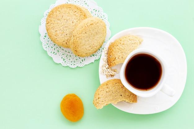 Glutenfreie hausgemachte haferkekse, trockene aprikosen und eine tasse tee oder kaffee espresso auf pastellgrün
