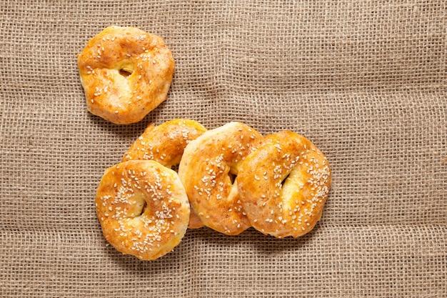 Glutenfreie hausgemachte kuchen. komposition im rustikalen stil. quarkringe oder bagels auf einer grob strukturierten sackleinen. draufsicht, nahaufnahme.