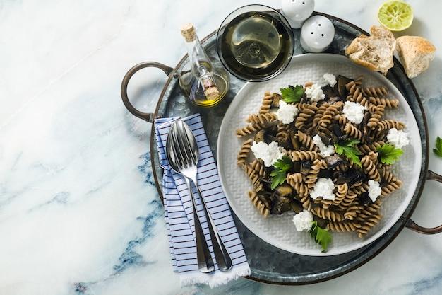 Glutenfreie nudeln aus halbweizen-farro-mehl mit portobello-pilzen und ricotta-käse auf einem tablett auf einem marmortisch. gesunde vegetarische rezepte