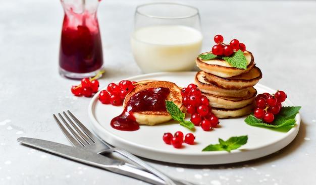 Glutenfreie pfannkuchen mit kirschmarmelade und roter johannisbeere