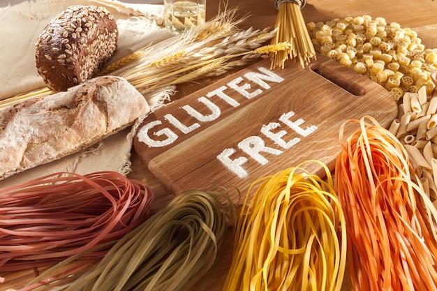 Glutenfreies essen. verschiedene nudeln, brot und snacks auf hölzernem hintergrund von oben. gesundes und diät-konzept.