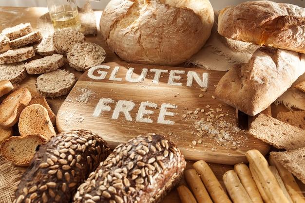 Glutenfreies essen. verschiedene nudeln, brot und snacks auf hölzernem hintergrund von oben