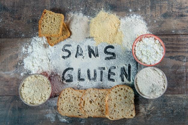 Glutenfreies (ohne gluten) brot und mehl auf hölzernem hintergrund