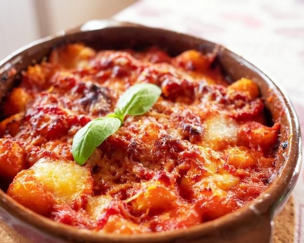 Gnocchi alla sorrentina, italienische kartoffelknödel in tomatensauce, überbacken mit mozzarella-käse in einer terrakottaschale. selektiver fokus.