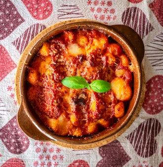 Gnocchi alla sorrentina, italienische kartoffelknödel in tomatensauce, überbacken mit mozzarella-käse in einer terrakottaschale.