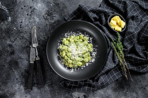 Gnocchi mit basilikum-spinat-sauce und parmesan. italienische kartoffelpaste. schwarzer hintergrund.
