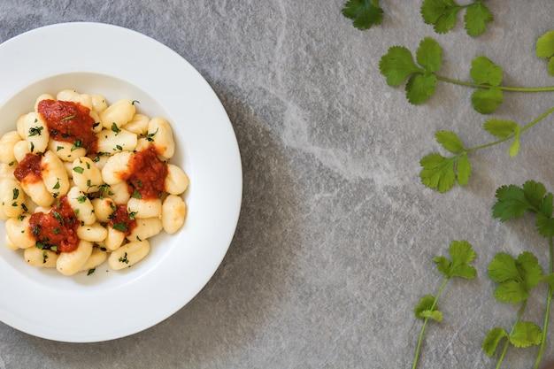 Gnocchi mit tomatensauce auf grauem stein, kopierraum