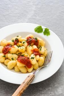 Gnocchi mit tomatensauce auf grauem stein