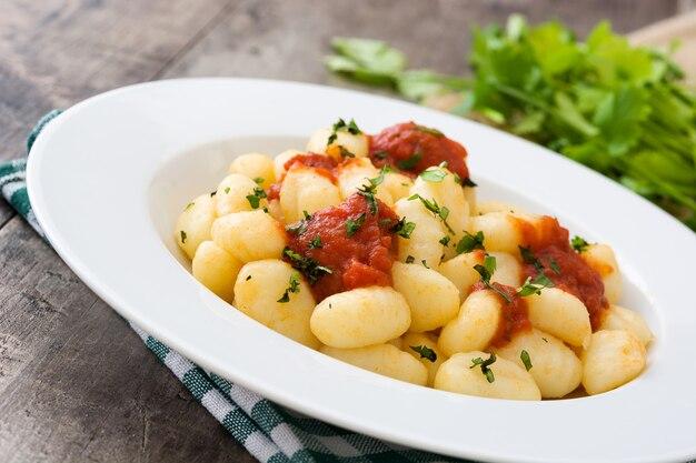 Gnocchi mit tomatensauce auf hölzernem hintergrund