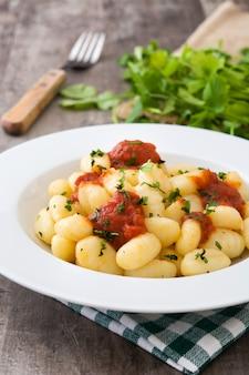 Gnocchi mit tomatensauce auf holztisch