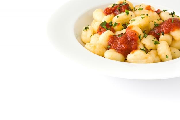 Gnocchi mit tomatensauce in der platte lokalisiert auf weiß.