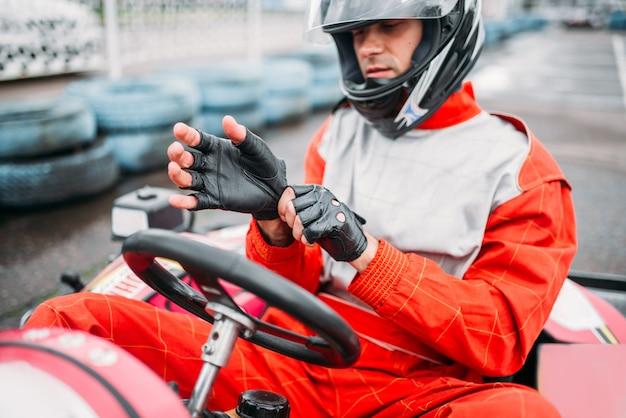 Go-kart-fahrer im helm auf kart-speed-track. karrenrennen