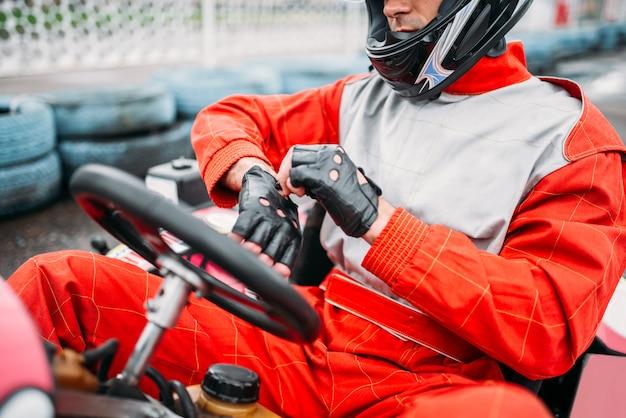 Go-kart-fahrer im helm auf kart-speed-track
