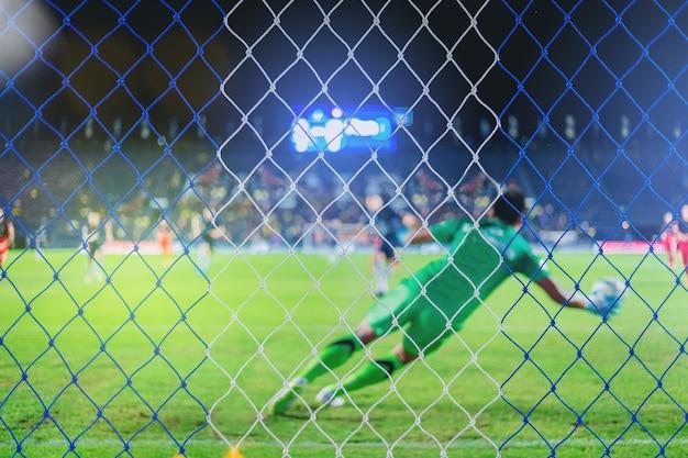 Goalekeeper und spieler während des elfmeterschießens im fußballspiel. wähle den fokus im netz aus