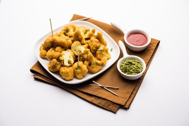 Gobi pakora oder phoolgobi pakoda aus frischem, in blumenkohl getauchtem kichererbsenteig und dann in öl frittiert. serviert mit tomatenketchup und minz-chutney. selektiver fokus