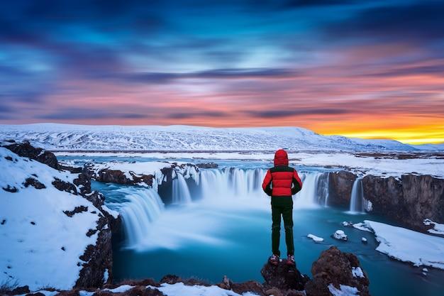 Godafoss wasserfall bei sonnenuntergang im winter, island. kerl in roter jacke schaut auf godafoss wasserfall.
