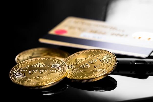 Gold-bitcoin am modernen handy auf holztisch