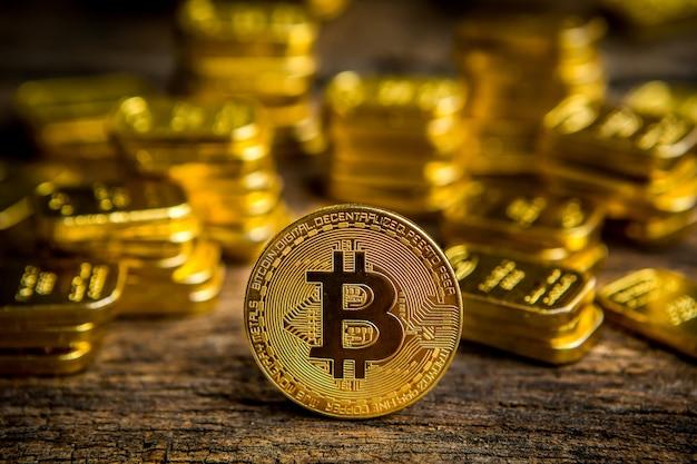 Gold-bitcoin-münze auf dem alten bretterboden mit goldbarrenhintergrund