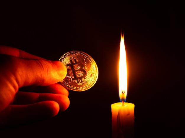 Gold-bitcoin-münze in der hand im warmen licht einer kerze auf einem dunklen hintergrund, virtuelles geld, kryptowährungskonzept.