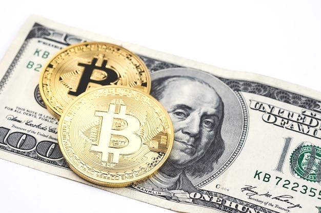 Gold bitcoin münzen auf hundert us-dollar rechnungshintergrund.