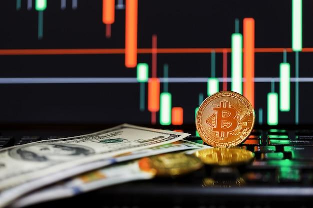 Gold-bitcoins vor dem hintergrund von business-charts in nahaufnahme und 100-dollar-scheinen.