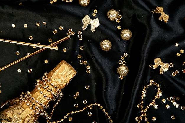 Gold champagnerflasche mit konfetti-sternen und party-luftschlangen auf festlichem schwarzem hintergrund