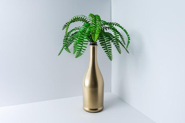 Gold champagnerflasche mit tropischen grünen palmblättern