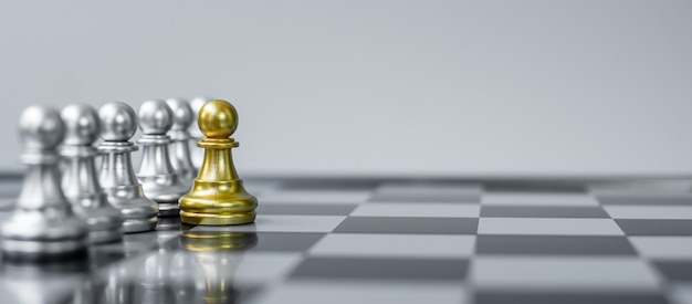 Gold chess pawn figur heben sie sich auf dem schachbretthintergrund von der masse ab.