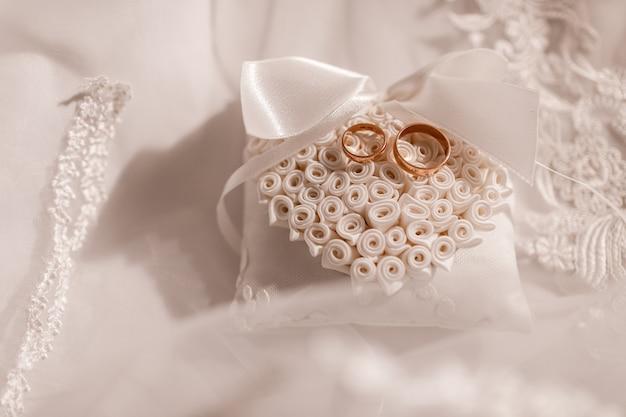 Gold eheringe auf einem spitzenblock. romantisches thema für jungvermählten. hochzeitszubehör