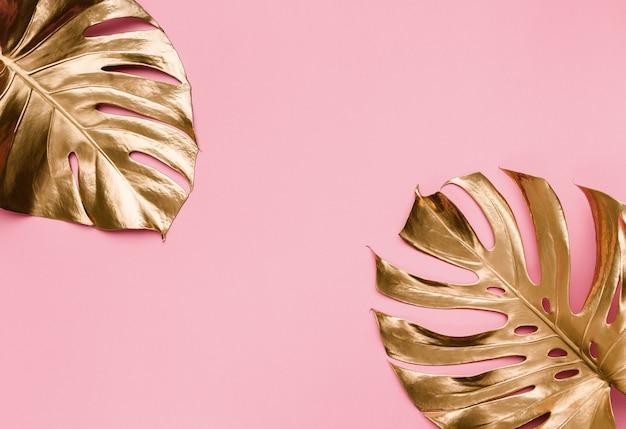 Gold gemalte tropische monsterblätter auf abstraktem pastellrosa hintergrund