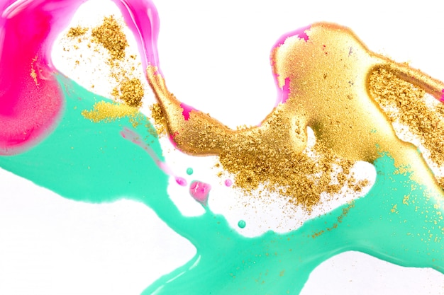 Gold-, grün- und rosatinten bespritzt auf weißem papierhintergrund. goldener glitzer