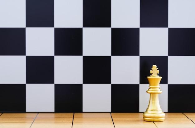 Gold king schachfigur stehen auf holzschachbrett, konzept des führungsspiels der strategie