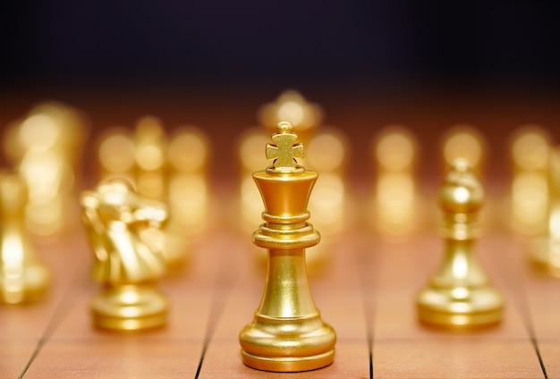 Gold king schachfigur und verschiedene schachfiguren stehen auf holzschachbrett, konzept des führungsspiels der strategie