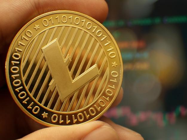 Gold lite münze von einer hand gehalten