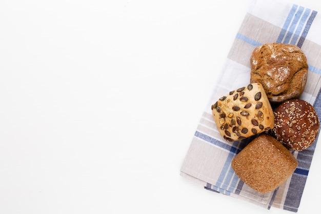 Gold rustikale knusprige brote und brötchen auf holztisch. stillleben von oben aufgenommen, flach gelegen.