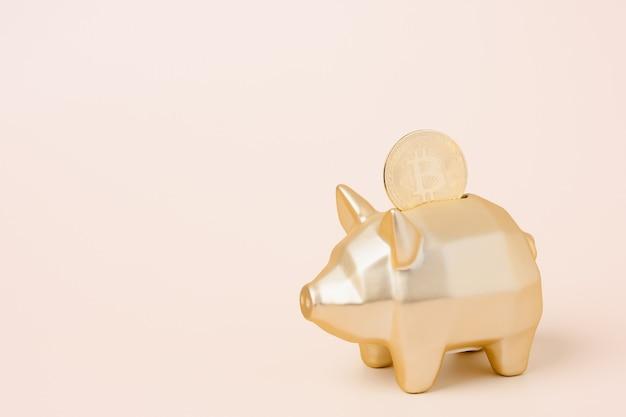 Gold sparschwein und goldene bitcoin auf goldgrund. kryptowährungseinsparungen.geld