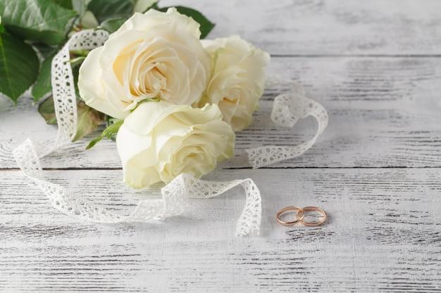 Gold trauringe auf einem strauß weißer rosen