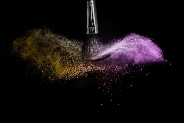 Gold und purpurrotes pulverspritzen im schwarzen hintergrund