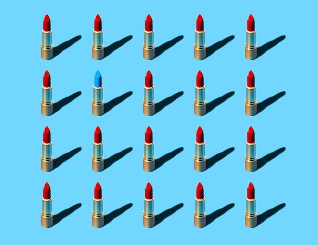 Gold und roter lippenstift, der muster mit einem blau auf pastellgrüner wand wiederholt