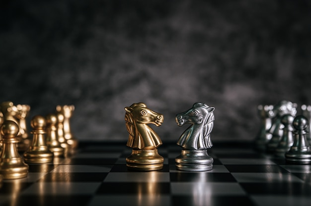 Gold- und silberschach auf schachbrettspiel für geschäftsmetapherführungskonzept
