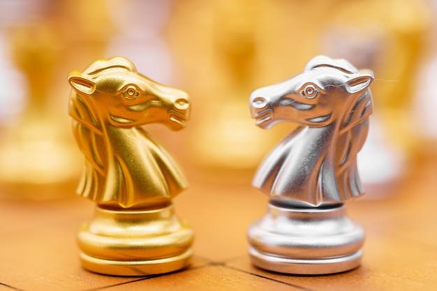Gold und siver pferd des schachspiels im spiel auf schachbrett