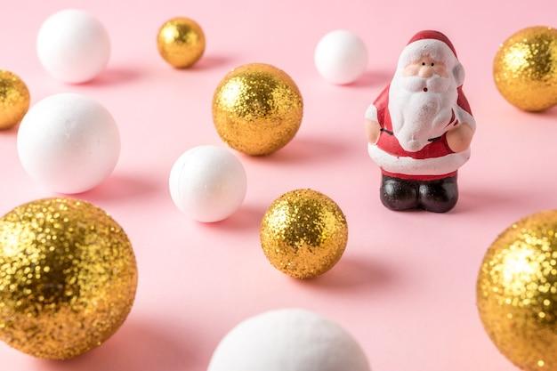 Gold und weiße glitzerkugeldekoration mit kleinem weihnachtsmann