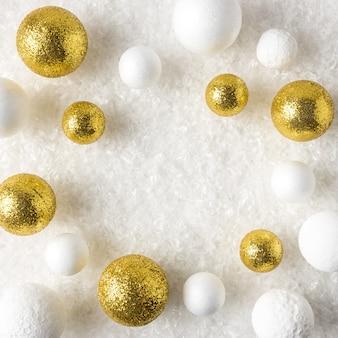 Gold und weiße glitzerkugeldekorationen im schnee