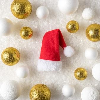 Gold und weiße glitzerkugeldekorationen mit weihnachtsmannmütze im schnee