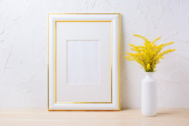 Gold verzierte rahmenmodell mit dekorativem gelbem blühendem gras im vase